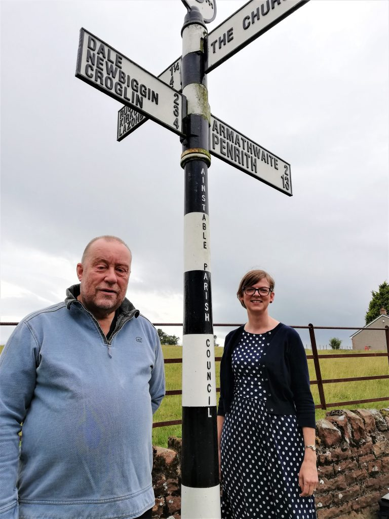Chairman and Clerk stand bu signpost at Ainstable Crossroads.